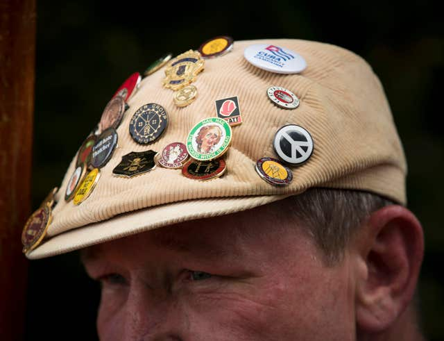 An activist's badge-covered flat cap