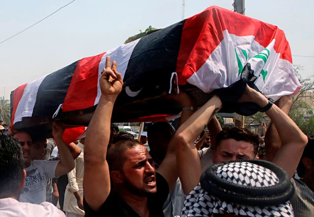Mourners carry the Iraqi flag-draped coffin of a protester