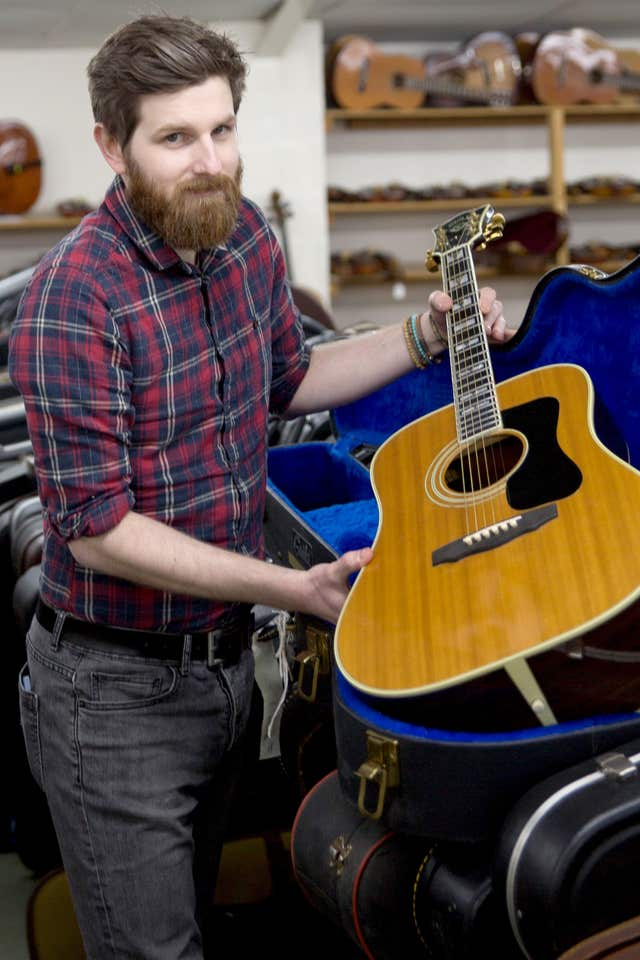 Luke Hobbs holding a guitar owned by Eric Clapton (Clare Hobbs Photography/Gardiner/PA)