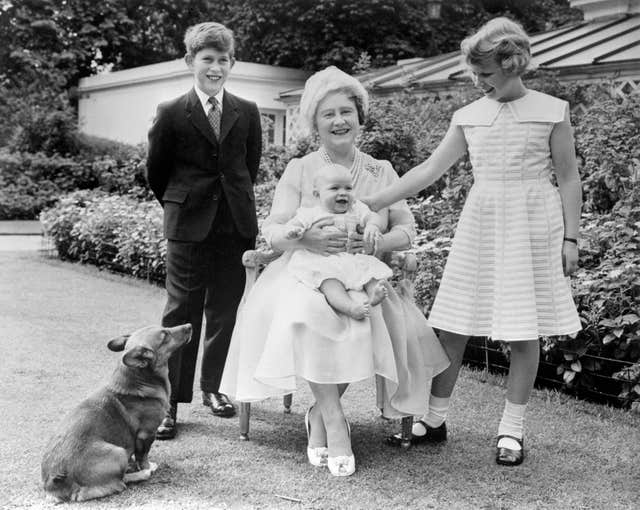 Prince Andrew smiles on the lap of his grandmother, the Queen Mother, as his brother, Prince Charles, and sister, Princess Anne, look on, in the garden of Clarence House, London (PA)