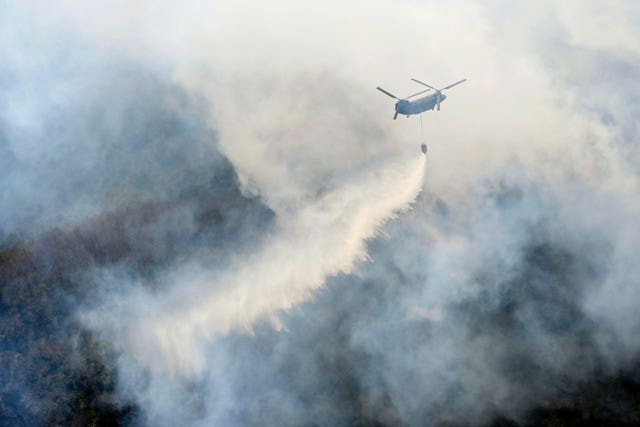 A helicopter dumps water on a wildfire