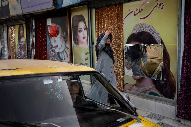 An Afghan woman walks past beauty salons with defaced window decorations, in Kabul, Afghanistan (Bernat Armangue/AP)