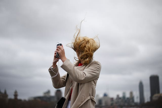 A tourist takes a photograph during strong winds on Westminster Bridge