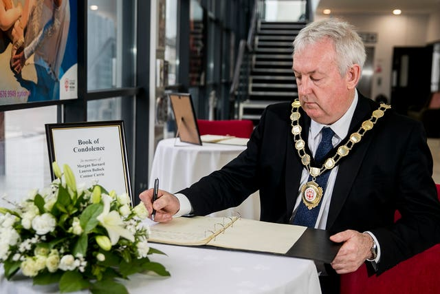 Councillor Sean McPeake, chairman of Mid-Ulster District Council, signing a book of condolence in Cookstown
