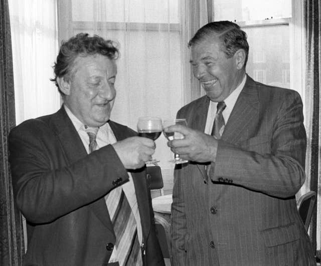 Moncrieff and PA's then-Parliamentary Editor Cyril Arthur toast one another in 1978 (PA)