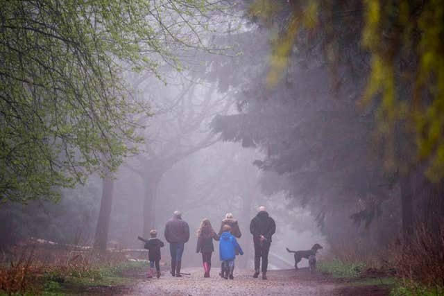 A family walk through the mist in Epping Forest, London, as the wet weather is set to give way to warm sunshine (Victoria Jones/PA)
