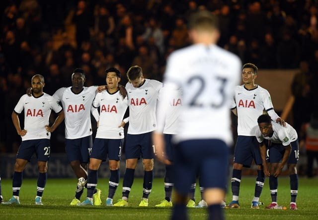 Tottenham's players wait as Christian Eriksen walks back after missing his penalty