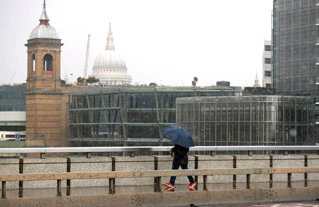 A person walking in the snow on London Bridge (Steve Parsons/PA)