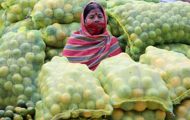 A fruit vendor wearing a face mask sits amid sacks of oranges at a wholesale market in Bengaluru, India