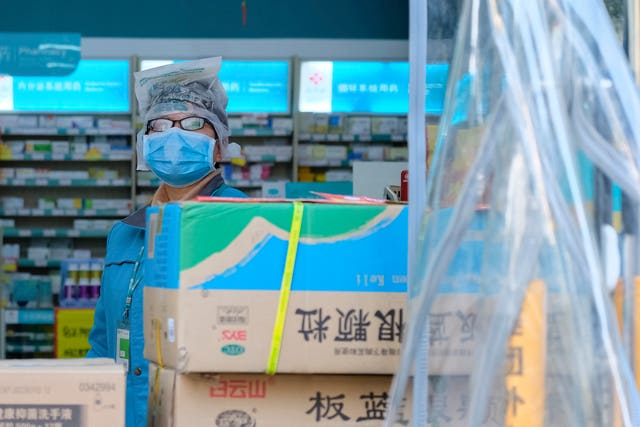 A clerk wearing a face mask and a plastic bag stands in a pharmacy in Wuhan in central China's Hubei Province