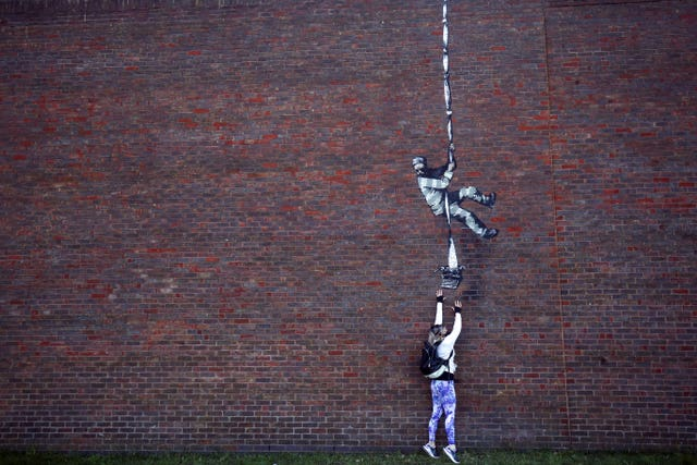 A member of the public looks at an artwork on the wall of the former prison in Reading (Steve Parsons/PA)
