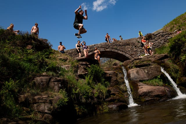People enjoying the good weather by Three Shires Head on the River Dane, where Cheshire, Derbyshire and Staffordshire meet (Jacob King/PA)