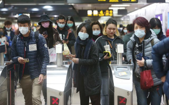 People wear masks at a metro station in Taipei