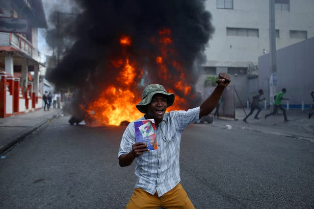 A protester kneels in front of a burning barricade with a copy of the Haitian Constitution