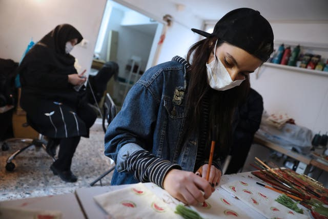 Bahareh Eskandarkhan paints on a cloth bag at a workshop of Bavar charity in Tehran, Iran, Monday, Nov. 23, 2020. As the coronavirus pandemic ravages Iran, a women's group hopes to empower its members by helping them make and sell face masks