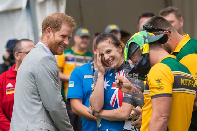 The Duke of Sussex reacts as Australian Invictus Games athlete Benjamin Yeomans puts a pair of swimming trunks on his head