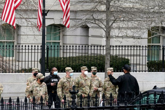 Members of the Army National Guard receive a briefing by US Secret Service police inside the White House complex (Gerald Herbert/AP)