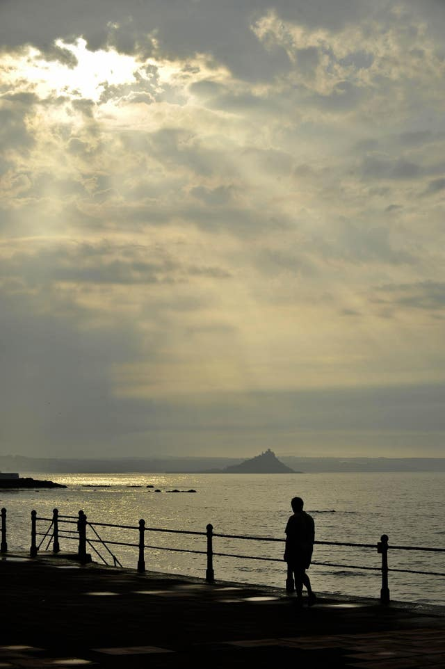 Early morning sunlight breaks through heavy clouds over Penzance