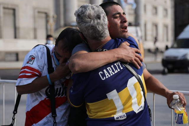 Fans of rival teams Boca Juniors, right, and River Plate, left, embrace