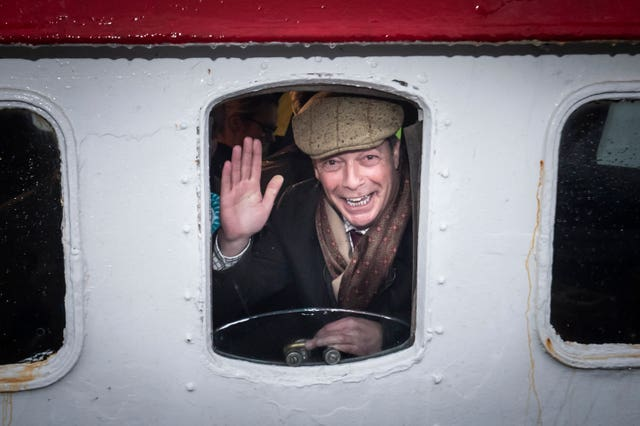 Brexit Party leader Nigel Farage looks out from a window on the Kestrel crabbing boat in Grimsby fish dock