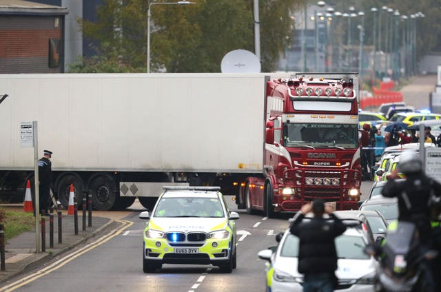 A lorry with attached container drives under police escort