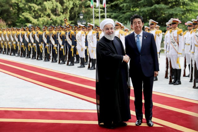 Japanese Prime Minister Shinzo Abe shakes hands with Iranian President Hassan Rouhani at the Saadabad Palace in Tehran, Iran