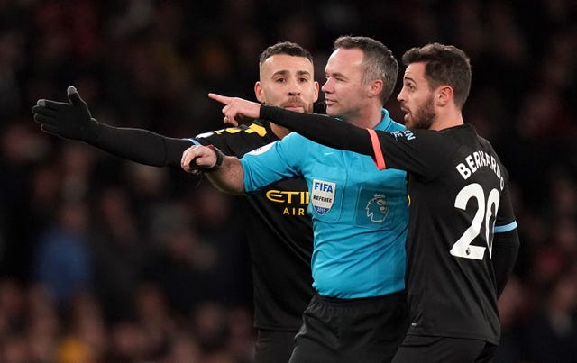 Manchester City's Nicolas Otamendi (left) and Bernardo Silva (right) speak with referee Paul Tierney during their victory over Arsenal